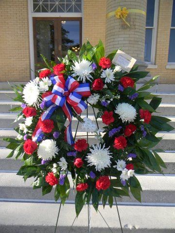 Imahe of wreath on stand, with greenery, white, red, and purple flowers and patriotic bow