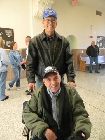 Man in blue hat pushes man in green jacket in wheelchair, both men smile for camera