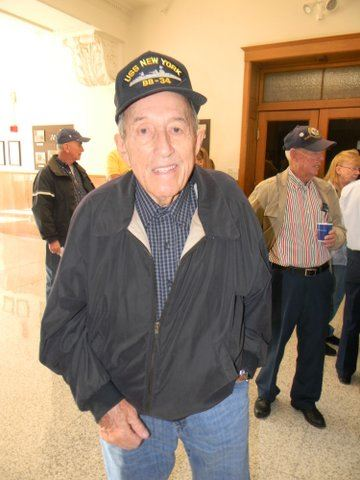 Man in black jacket and USS New York hat smiles for camera, standing in Court House hallway