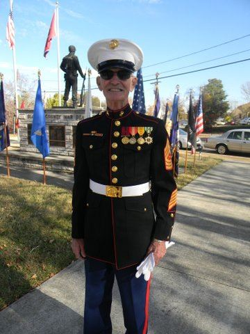 Older man in decorated Marine uniform smiles for camera