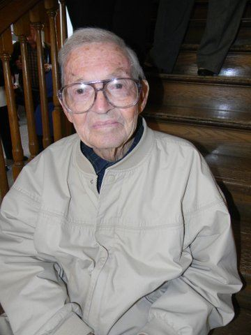 Man in khaki jacket and glasses smile for camera, sitting on steps