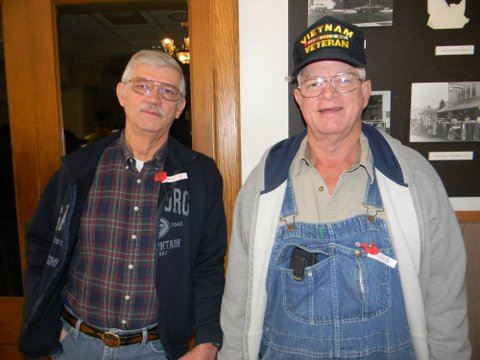 Man in glasses and blue jacket stands beside man in overralls and Vietnam Veteran hat, both look into camera