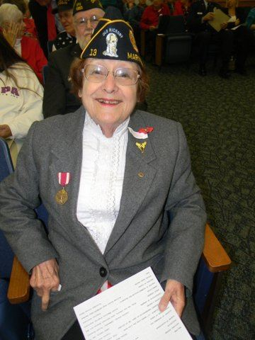 Woman in white shirt and grey suit with medals on lapel smiles while sitting in chair