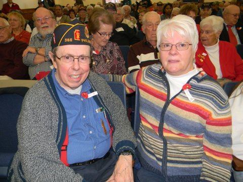 Two sitting participants, on in blue and one in multi-colored striped sweater, smile at camera