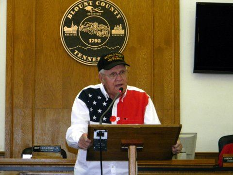 Man in red, white, and blue shirt and black hat  speaks at wooden podium