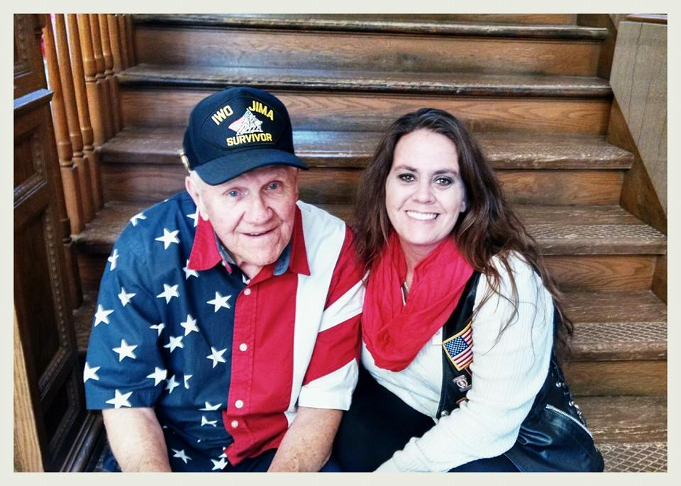 Man wearing Iwo Jima Survivor hat and American flag shirt smiles, sitting on wooden steps with smiling yong woman