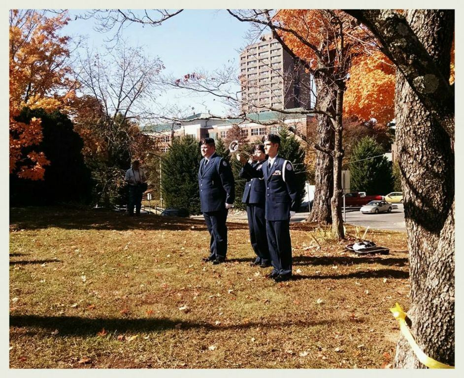 Three cadets, one playing trumpet, stand on lawn under trees