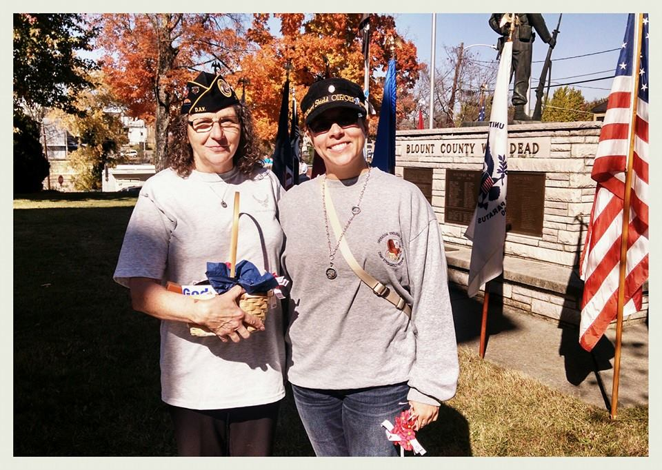 Two women smile and stand together otuside, one in veteran's cap