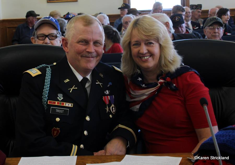 Man in Army decorated dress unifrom smiles with lady in red beside him, both sitting