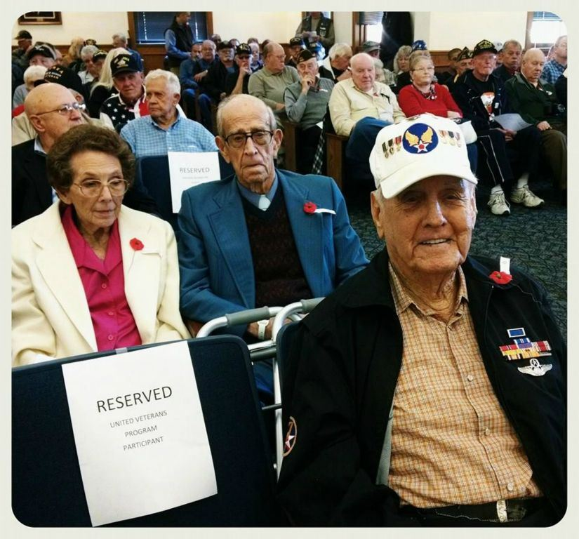 Up close of audience of participants, all with poppy pins, sitting in court house room
