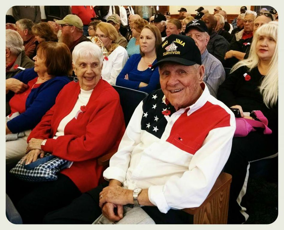 Man wearing patriotic shirt and Iwo Jima Survivor hat smiles for camera, sitting in Court house room