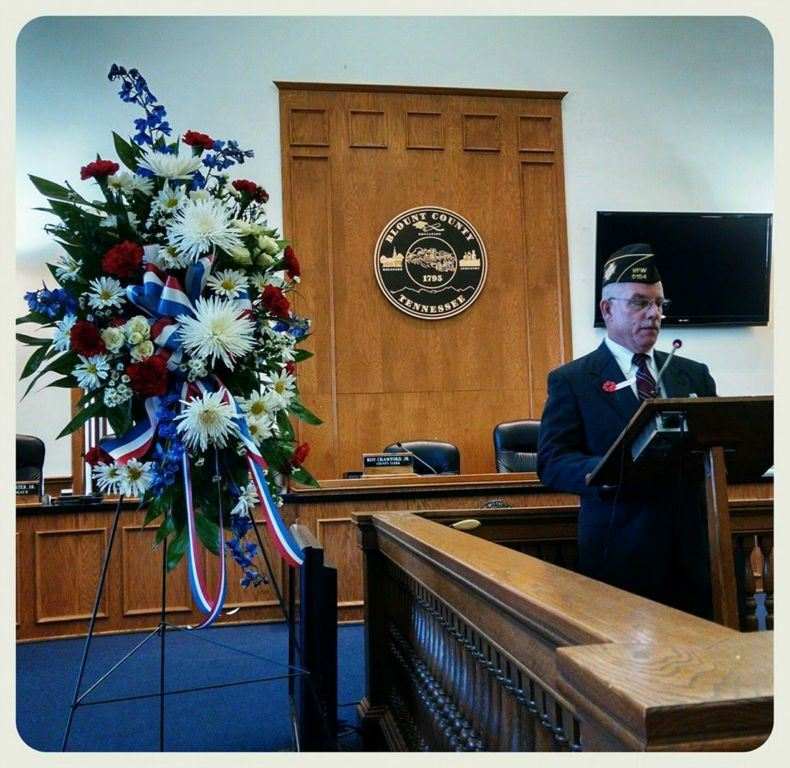 Man at wooden podium speaks, patriotic wreath is beside him