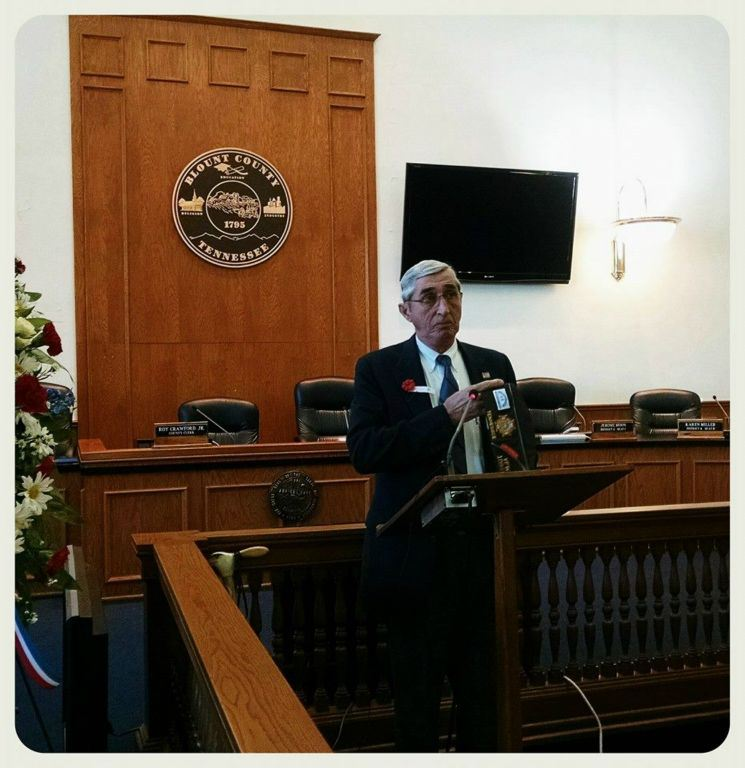 Man stands at wooden podium in courtroom, wearing suit and glasses