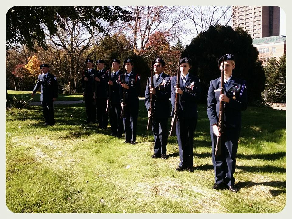 Seven cadets in dress uniform hold firearms in front of their bodies, standing on lawn