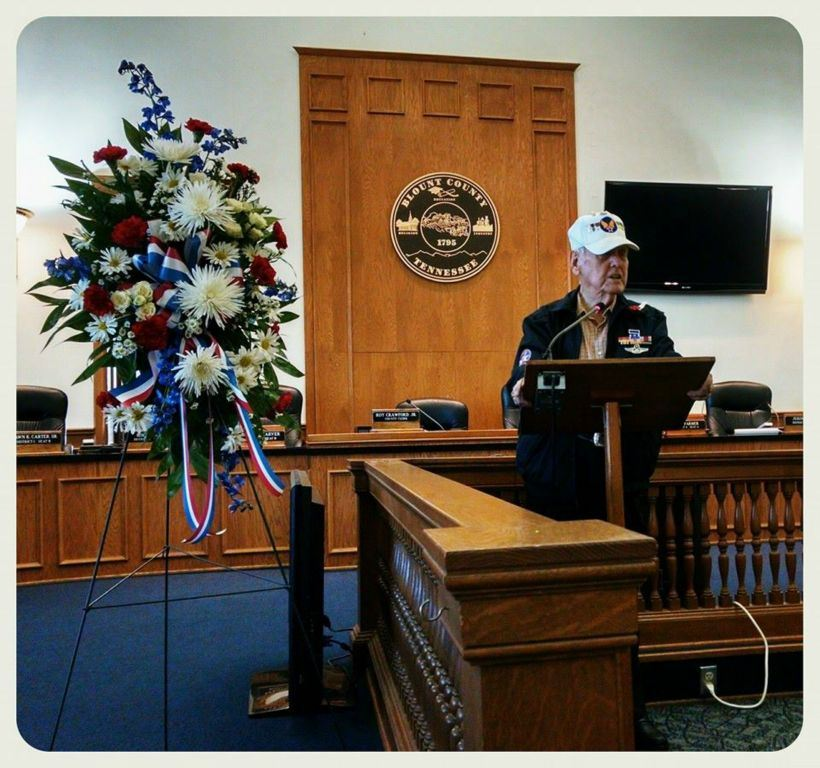 Man in white veteran's hate stands speaking at wooden podium, with potriotic wreath at his side