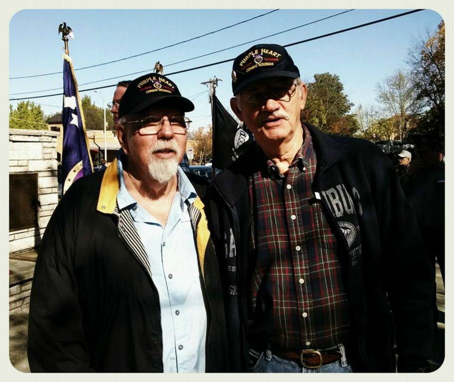 Two men wearing Purple Heart hats stand beside in each other outside in fron to f memorial