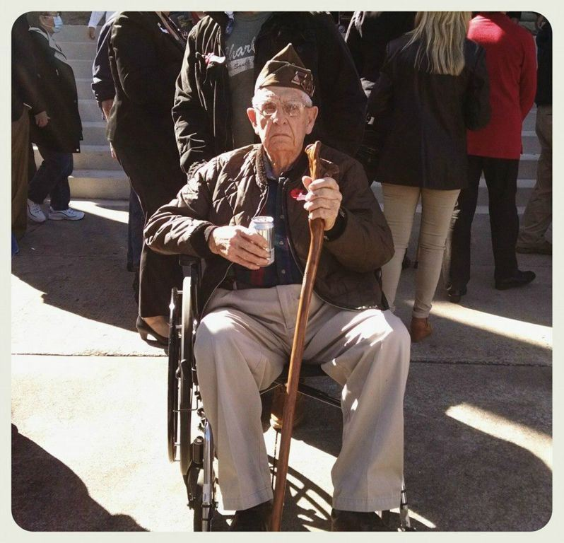 Veteran in khaki sits in wheelchair, holding wooden cane
