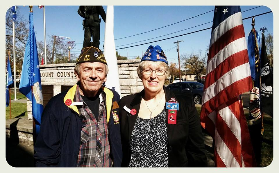 Man and woman, both wearing poppy pins and veteran caps stand beside each other in fron of Blount County War Dead memorial and flags