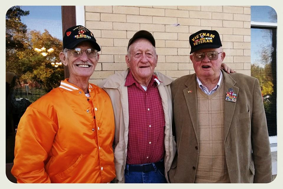 Three men stand beside each other with arms around one anoher smiling at camera, all three wear black veteran hats