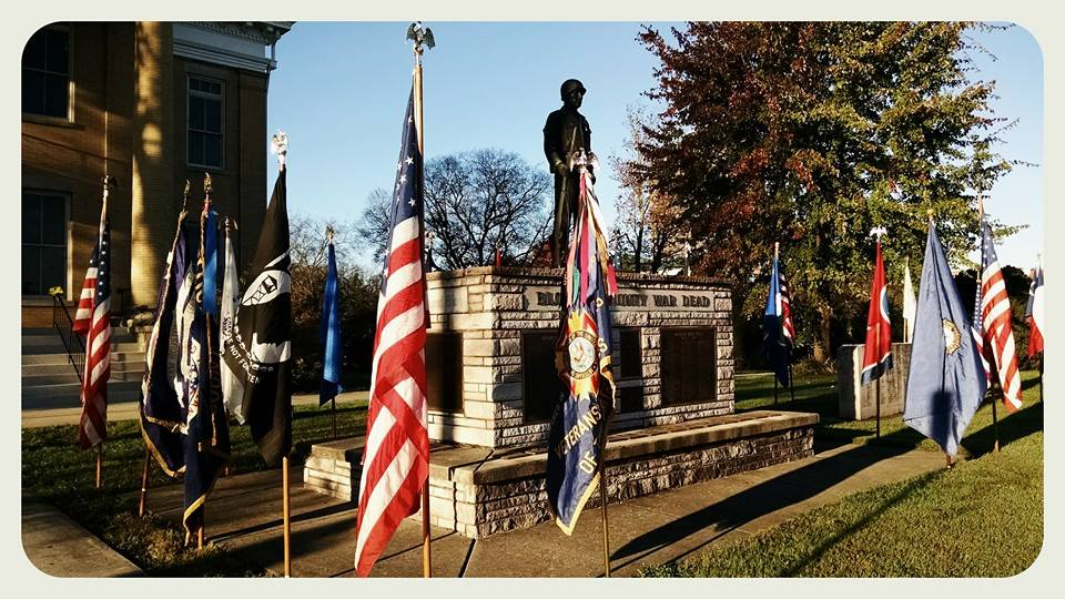 Side view of Blount County War Dead Memorial with flags at perimeter
