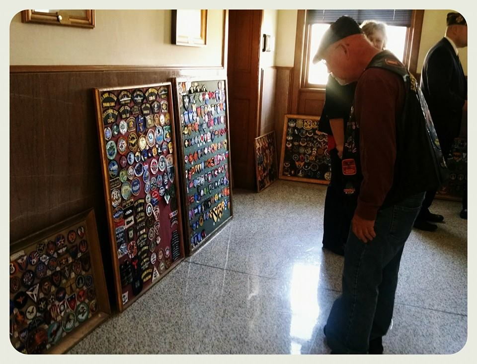 Man looks at boards full of military patches on display in hallway