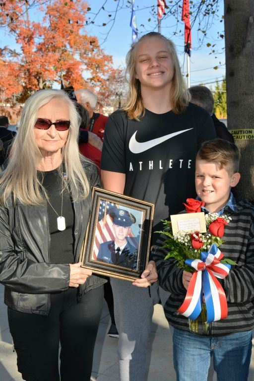 Woman stands with two boys, holding framed picture of marine, and one boy holds vase of roses