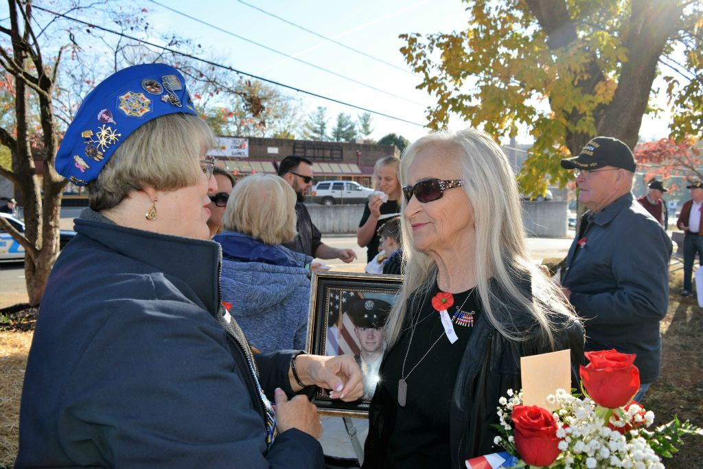Woman in blue cap speaks to woman holding framed picture of marine