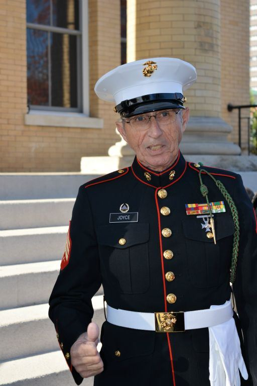 Man wears Marine dress uniform, giving thumbs up, standing on steps of Court house