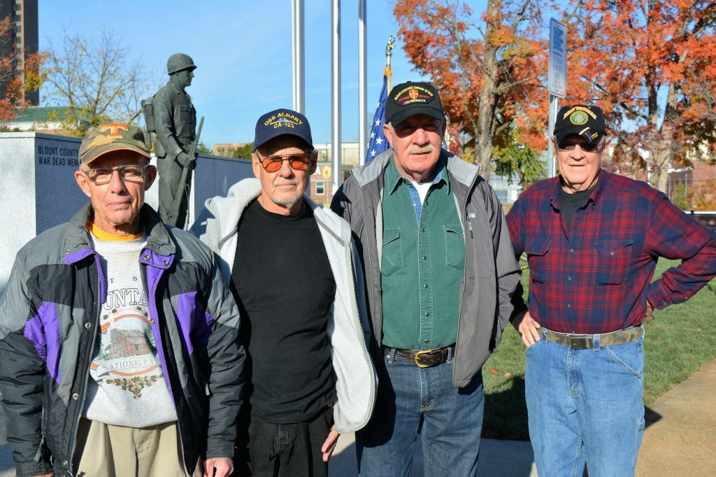 Four men stand in a line outside, all looking to camera, memorial is behind them
