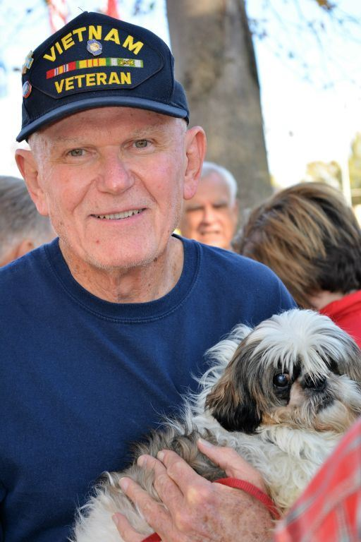 Man wearing blue shirt and Vietnam veteran hat holds small white dog, smiles into camera