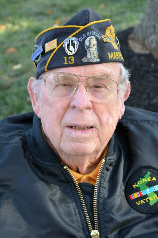 Man in glasses wears black jacket with Korea Veteran jacket and hat