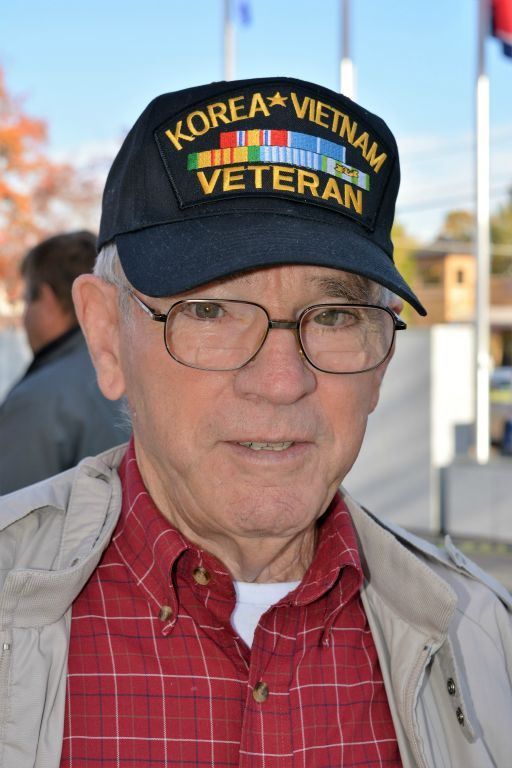 Up close image of man in red plaid shirt wearing glasses, and black hat saying Korea Vietnam Veteran