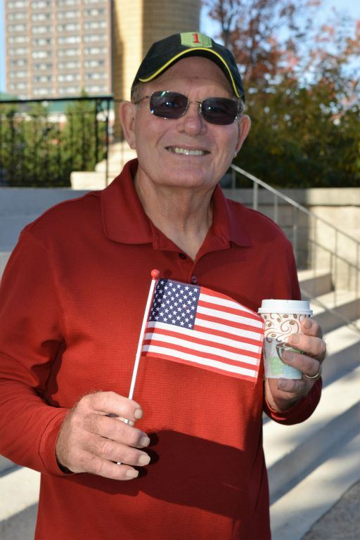 Man wearing red shirt, holds miniature American flag, wears Big Red One hat smiling into camera