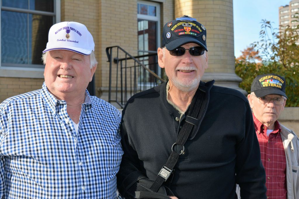 Three men stand outside Court house, one with Purple Heart combat wounded hat, one with Vietnam Veteran hat, and one with Korea Vietname Veteran hat