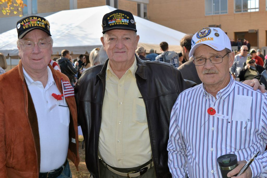 Three men stand together, the middle man has arms around shoulders of other twom all weariing veterans hats