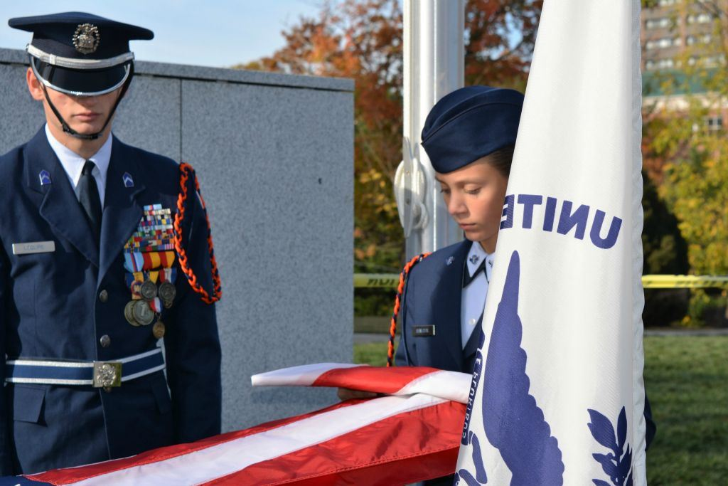 Two cadets in dress uniform unfold American flag