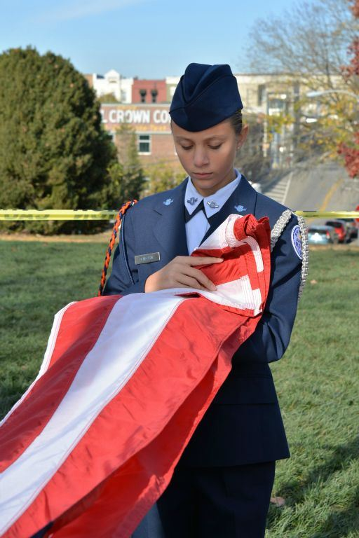 Female cadet in dress uniform unfolds American flag