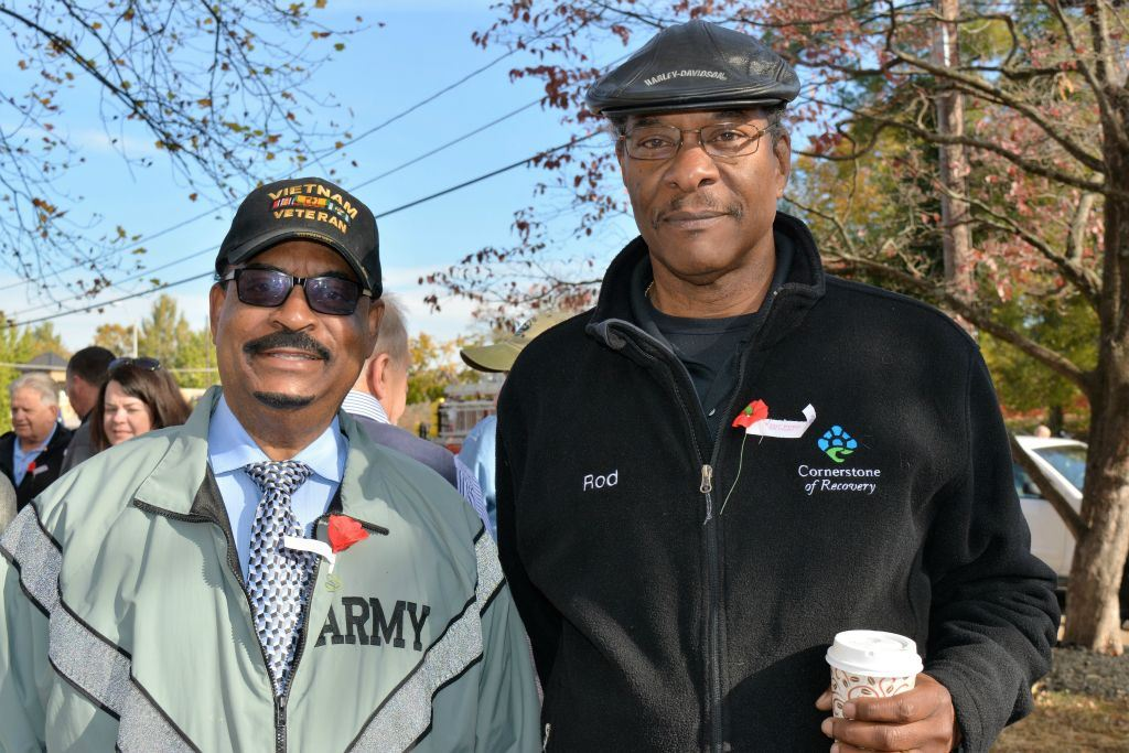 One man wearing army jacket and Vietnam Veteran hat stands beside another man in black with coffee cup in hand