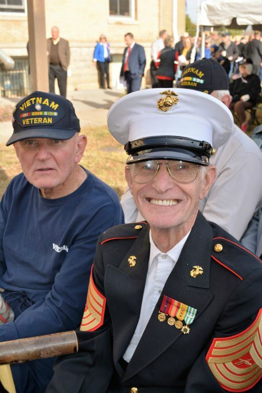 Man  wears Vietnam veteran hat, sitting beside man in Marine corps dress unifrom who is smiling into camera