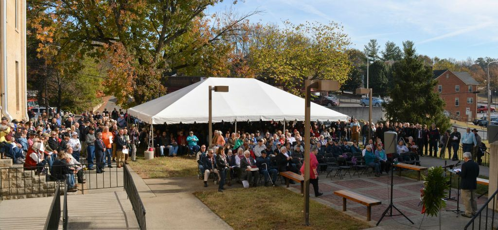Image from afar of tent, crowd, and speaker at the dedication ceremony of the memorial in front of Court house