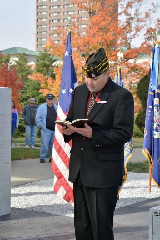 Man in black suit with red shirt reads from book outside of memorial