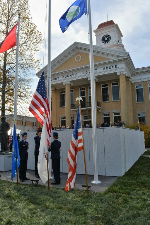 Three cadets raise the American flag in front of new memorial
