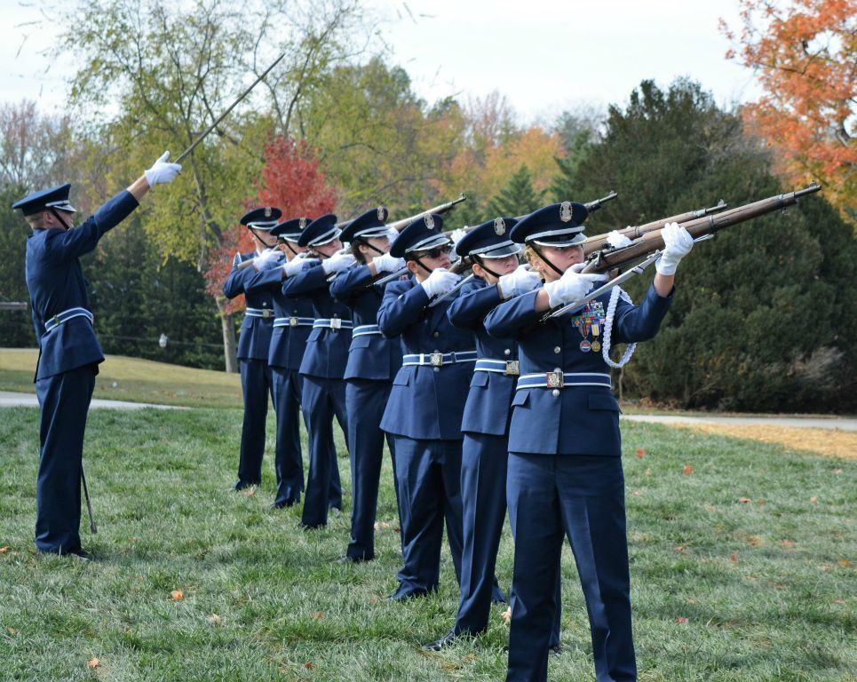 Line of cadets in dress uniform aim firearms, at lead is cadet with saber