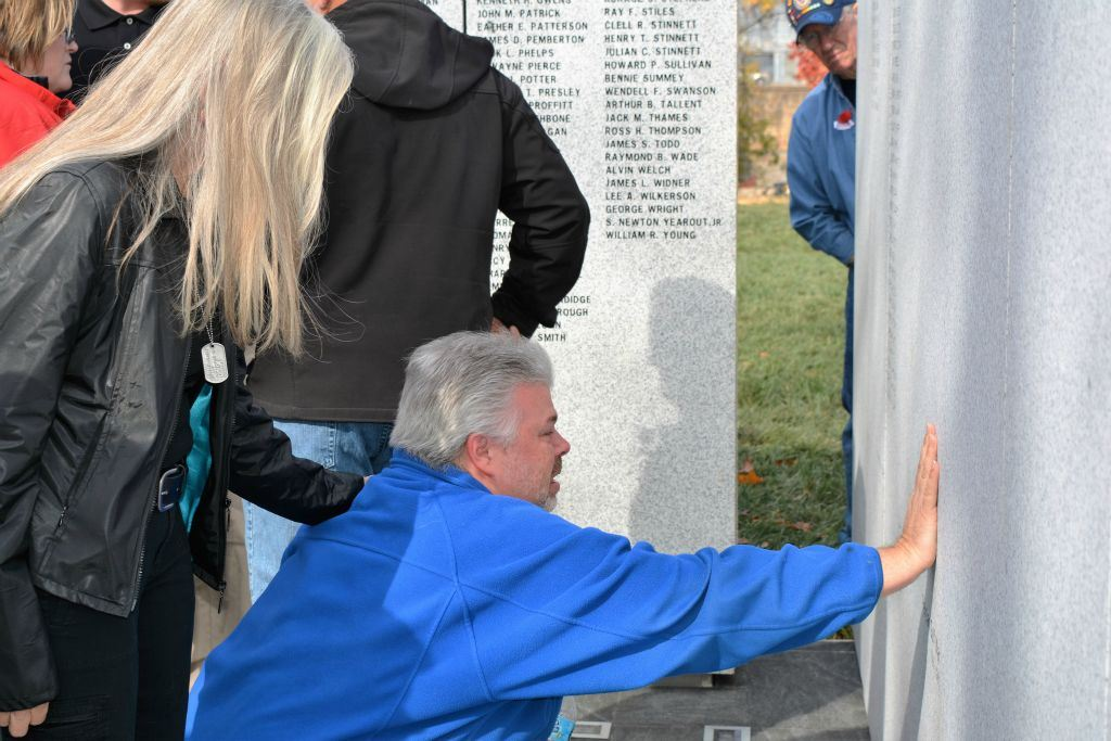 Man in blue kneels on ground with hand on memorial stone, with woman in black offering comforting arm on his shoulder