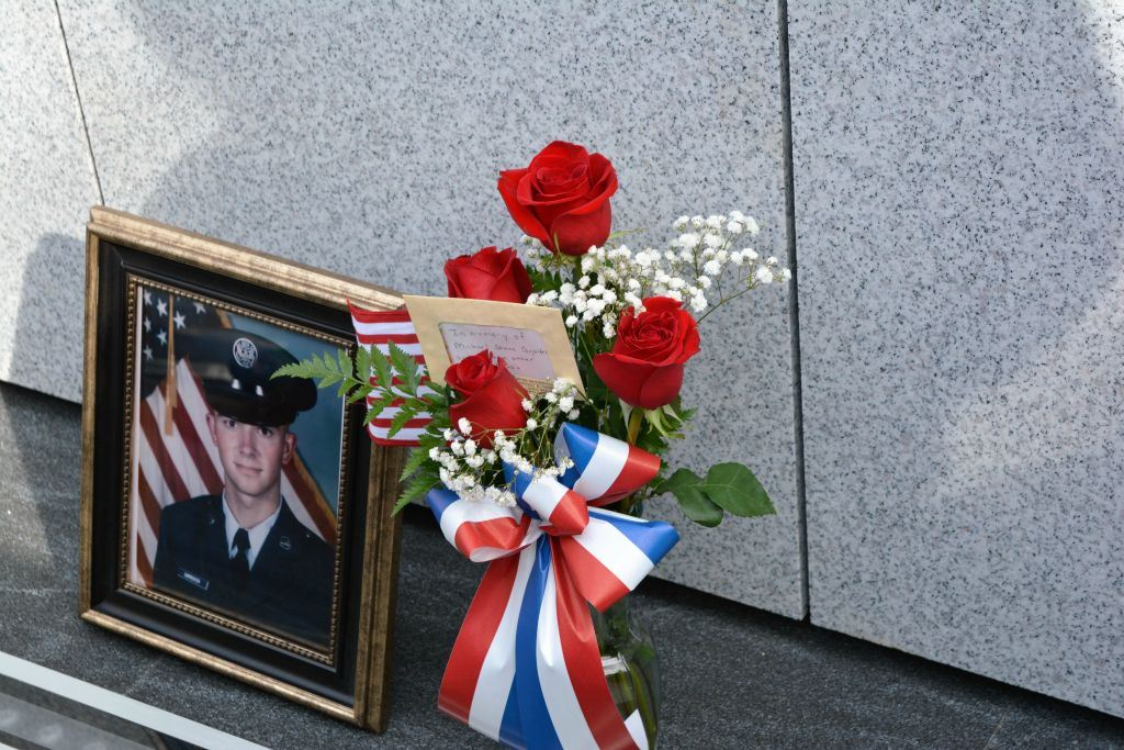 Framed picture of marine sits beside vase of roses at base of memorial