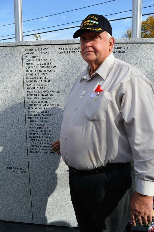 Man wearing Vietnam Veteran hat stands with hand on name engraved in memorial stone