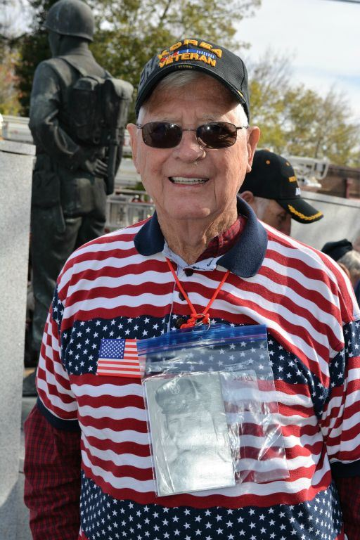 Man with American flag shirt and Korea Veteran hat wears black and white photograph around his neck in a plastic bag