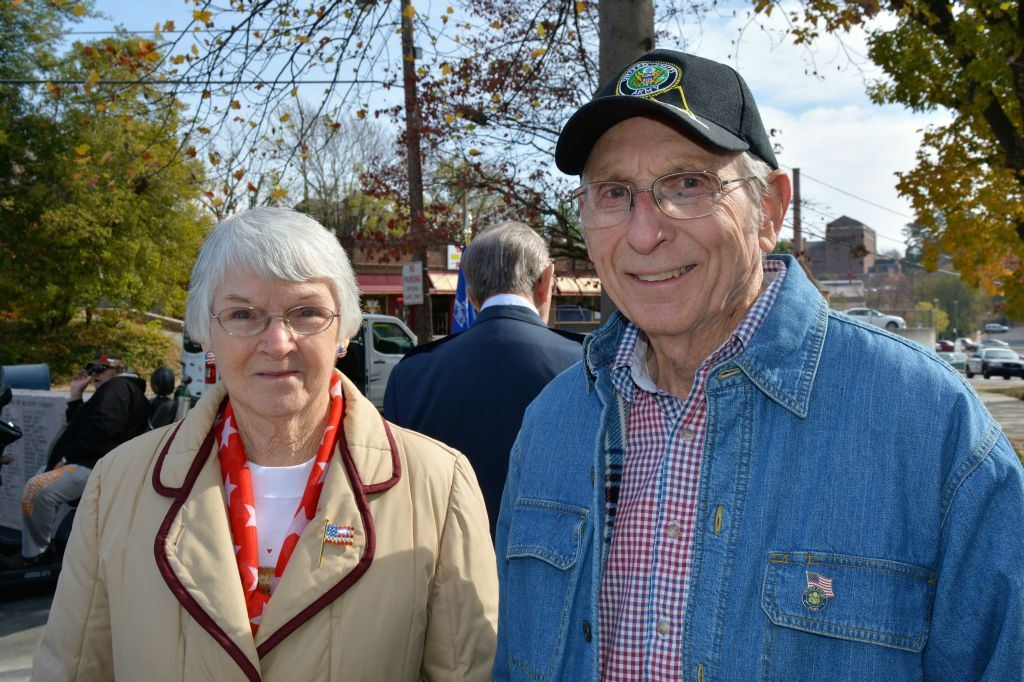 Woman in khaki jacket stands beside man in jean jacket and army hat, both look into camera smiling