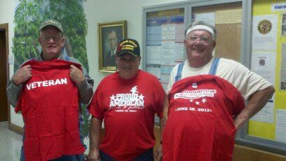 Three men wear or hold up red shirts with veteran, proud America text on them