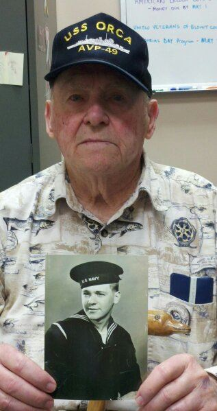 Up close picture of veteran, wearing USS Orca hat, holds up black and white picture of navyman, and looks into camera